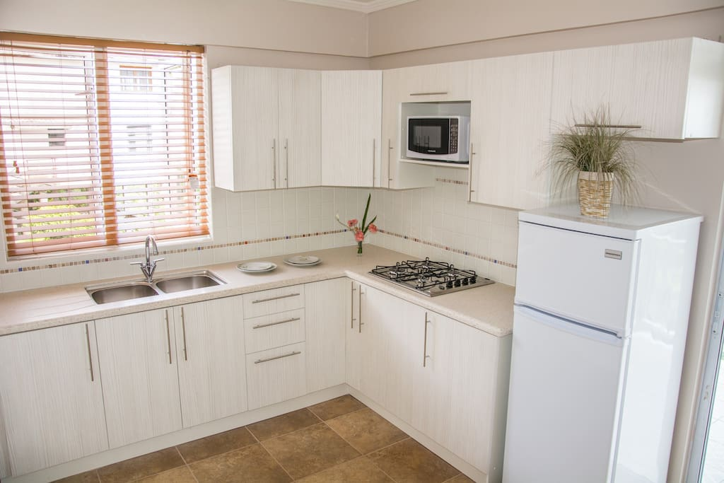 Clean kitchen with microwave oven, refrigerator, stove top, cutlery and other utensils