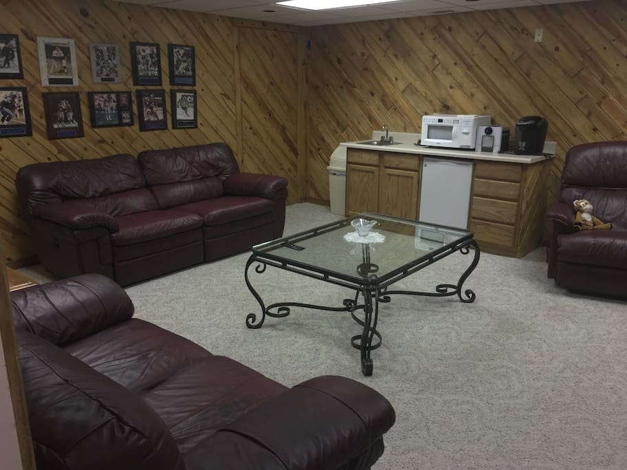 Different angle of living room area. Provided with microwave, keurig coffee maker and stocked fridge with beverages.