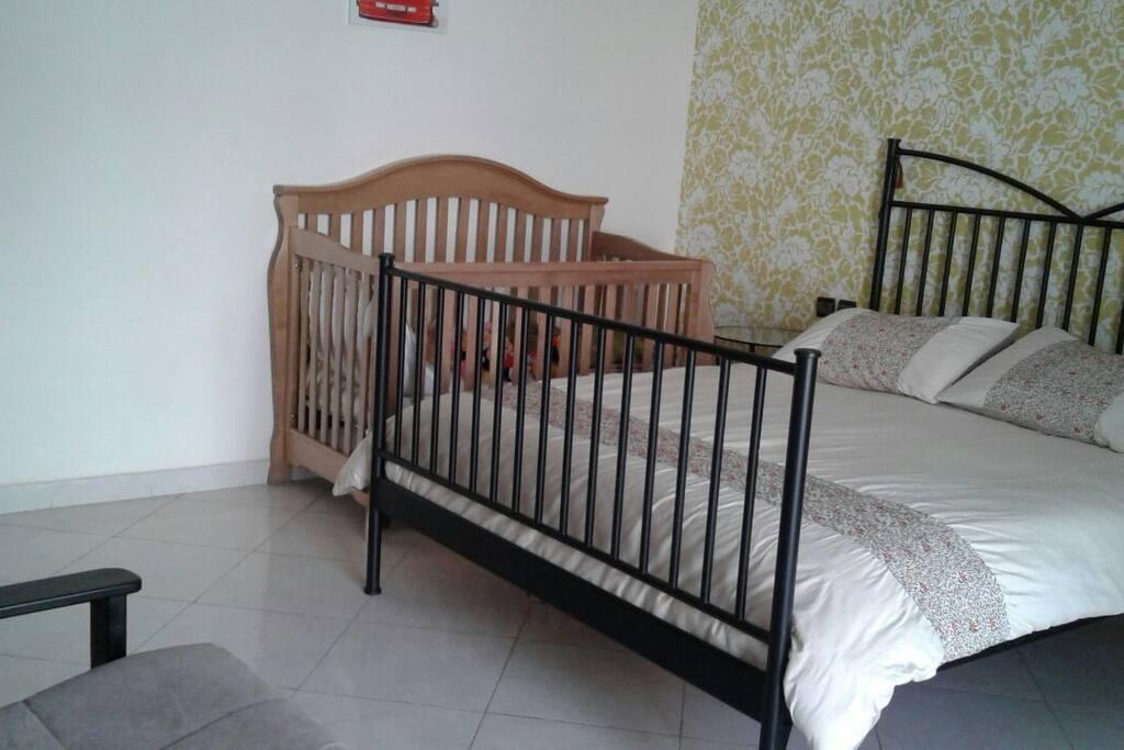 Chambre avec lit de bèbè et balcon et lit pliable