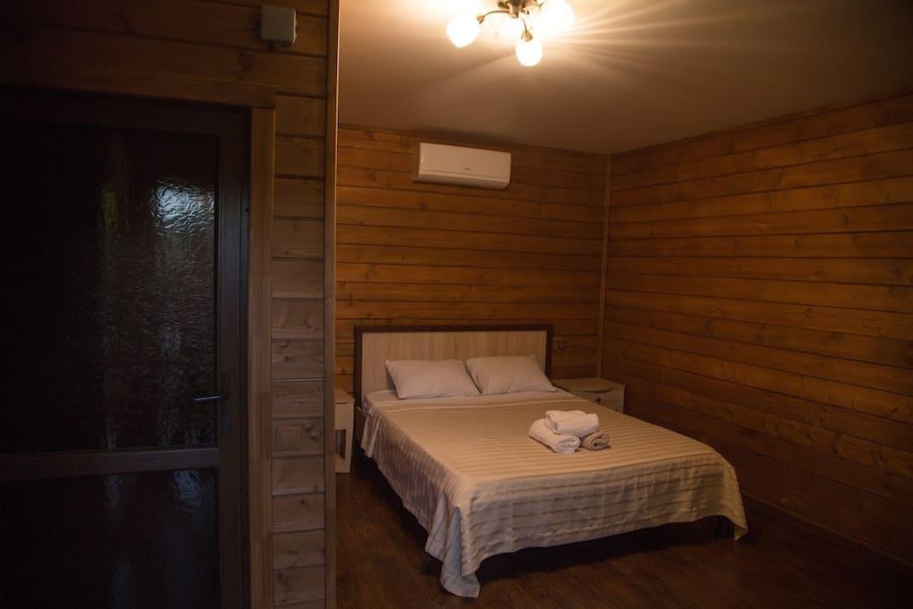 Большая двуспальная кровать, кондиционер, две тумбочки и ванные принадлежности