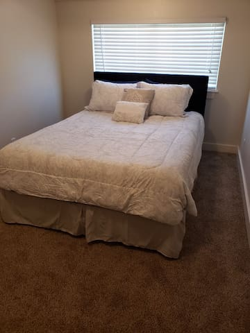 1st bedroom with a queen bed and a dresser.
