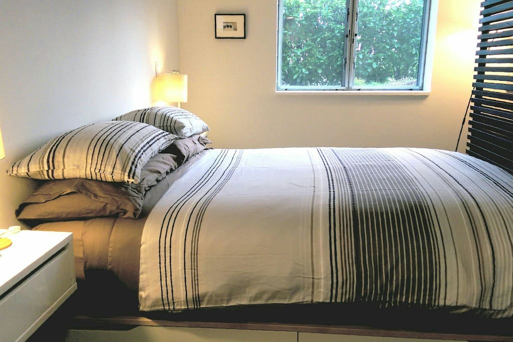 Down bedding and Consumer Reports top-rated mattress. Privacy and greenery looking out onto the side yard.