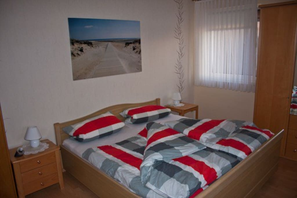 Schlafzimmer mit Doppelbett und Beistellbett
