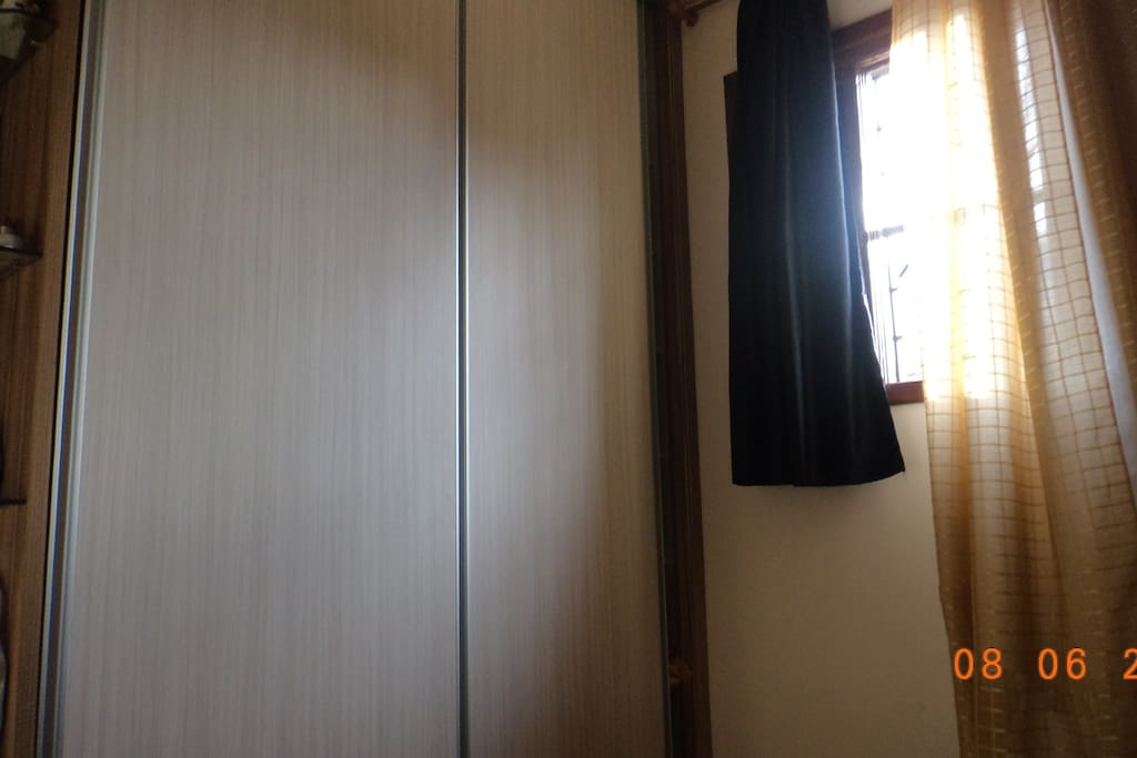 In this picture you can see an wardrobe with two doors and the window.