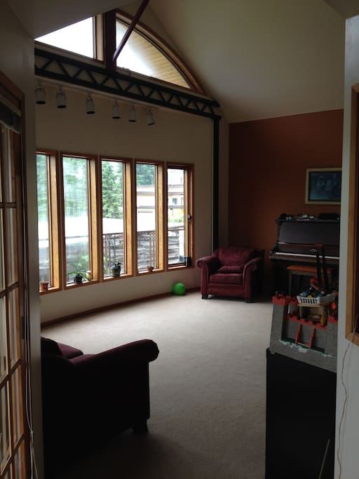 standing at the door to the porch, looking into the living room with vaulted ceilings