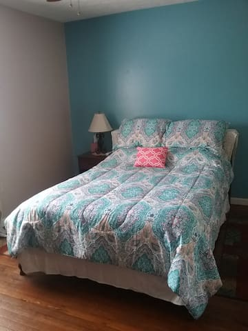 Bedroom 1- downstairs. Double bed, nightstand, lamp, chest of drawers, towel rack, ceiling fan, walk in closet with hangers.