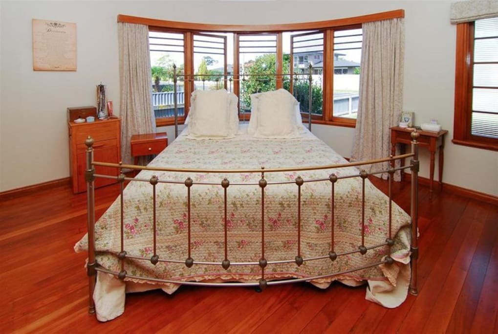 Your Master Bedroom. Rounded windows, polished native timber floor and a beautiful bed.