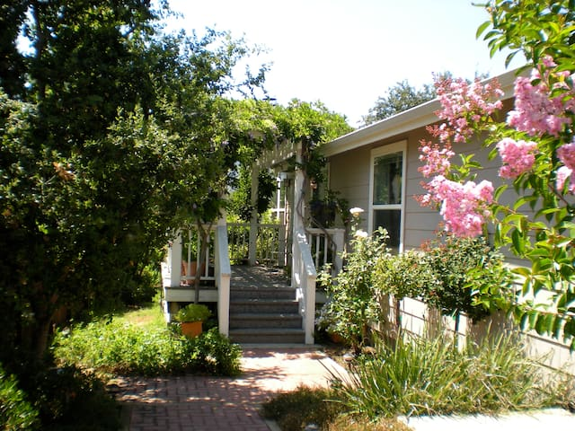 Enter through the gate to a secluded garden with brick walkway to house. Lined with fountains trees and flowers.