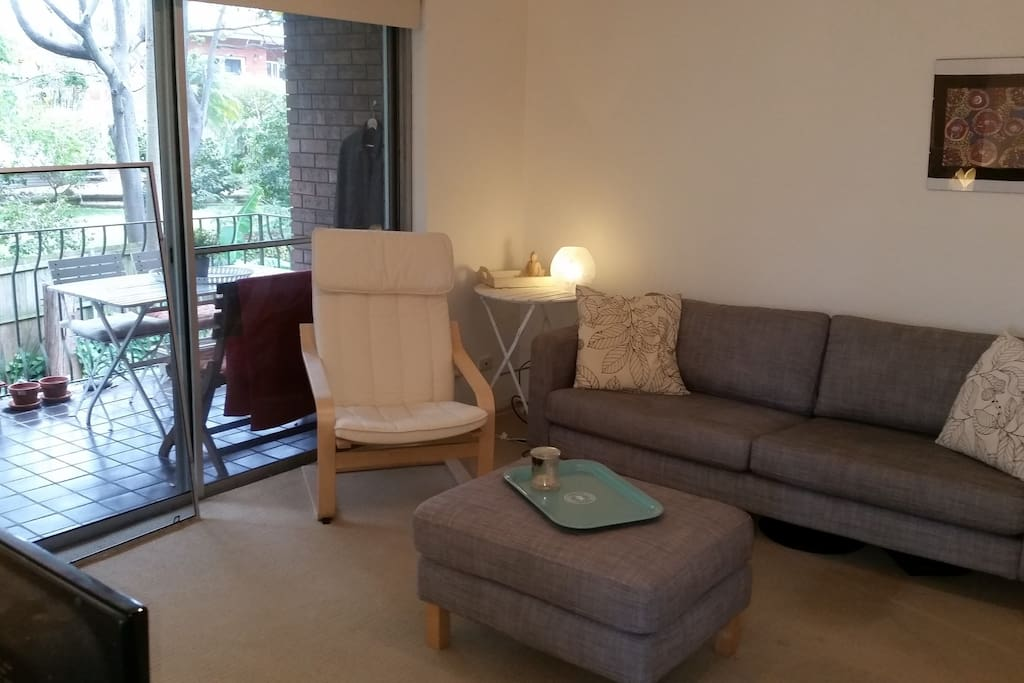 Living room with comfy couch leading to huge balcony