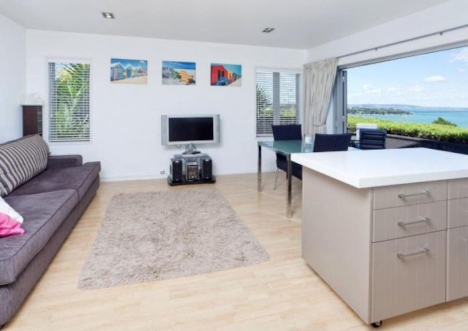 Open plan living, dining & kitchen area with bi-fold doors that open fully to the deck and sea views. Complimentary wifi. A 40inch flat screen also provides complimentary Netflix. You can also BYO Sky card if you have one.