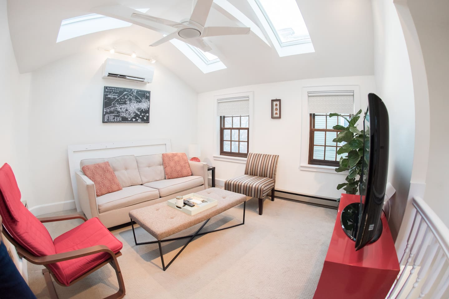Airy and bright living room with vaulted ceilings. Couch converts into a queen bed. Living room is on second floor.