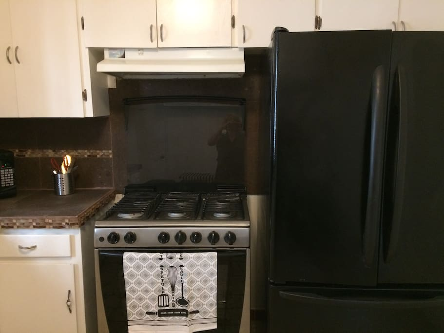 Kitchen has stove, refrigerator, toaster, coffee grinder, waffle maker, micro, etc.