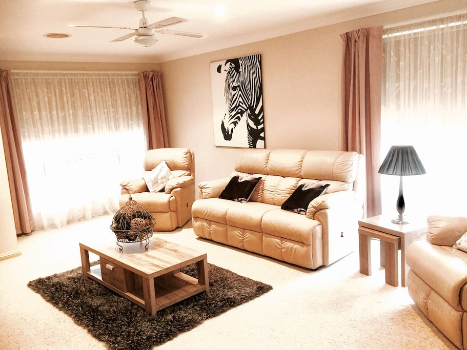Spacious lounge area with leather lounges and 2 recliners