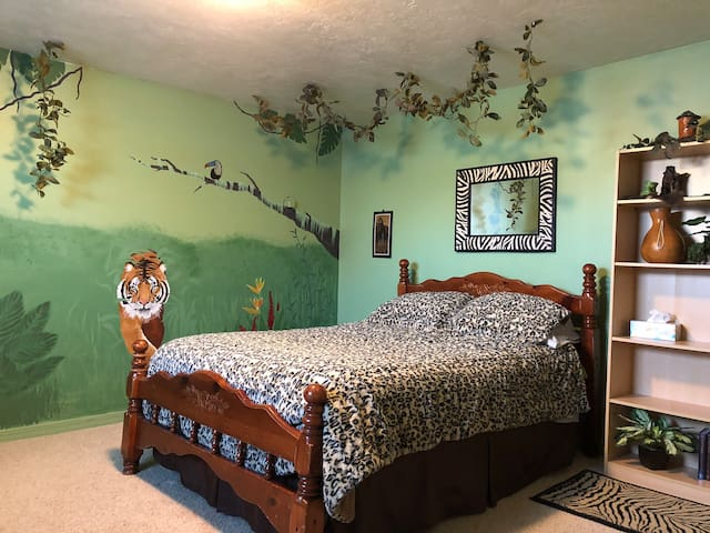 Jungle themed room with nice queen bed and dresser. The room is big enough to set up a travel crib or just spread out.