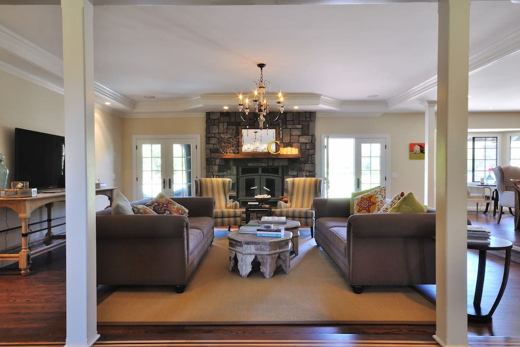 Formal living room with designer furnishings:  two deep and comfortable sofas and two arm chairs for relaxing and connecting with family and friends in front of the fire or while watching a movie on the 60 inch HDTV