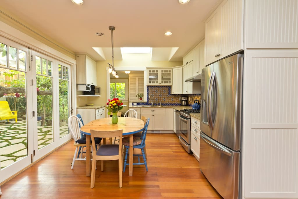 Kitchen dining area with skylight and large glass door to the backyard patio