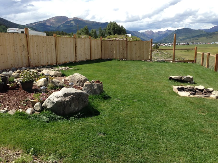 Fenced in yard with views of the mountains and town.