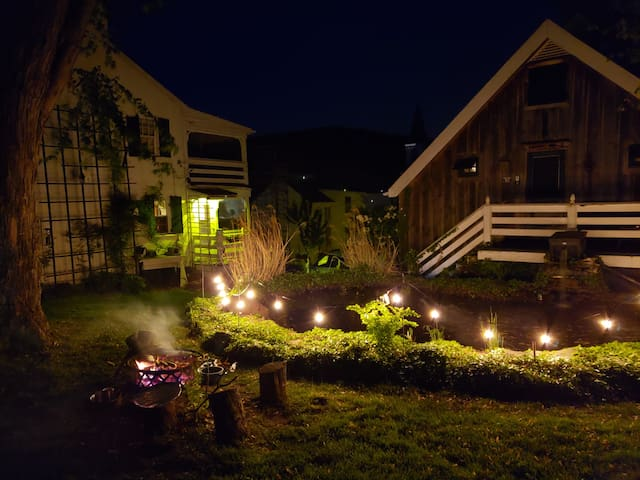 Nighttime view of the gardens with the cottage, campfire, and water garden (that's the owner's house on the left). We grill on the campfire and guests are welcome to do so as well. We have fire wood on site that's free for guests' usage.