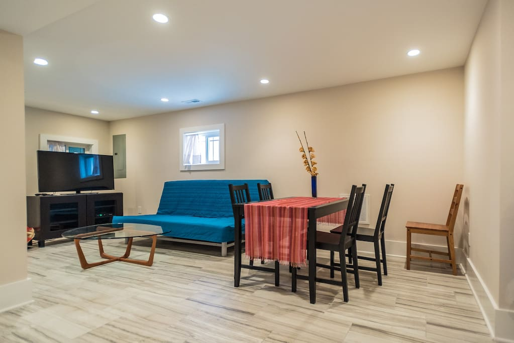 Spacious open living room with dining area, TV, and kitchenette