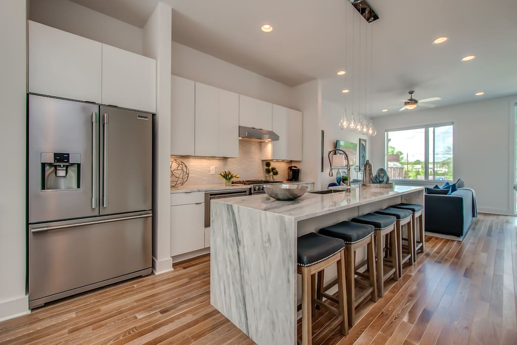 As practical as it is pretty, the crisp white kitchen boasts marble countertops and stainless steel appliances, including gas range and French door refrigerator.