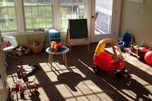 Playroom on first floor with many toys, plus a door to the backyard.