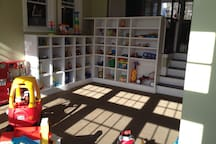 View of playroom shelves, stocked with toys.