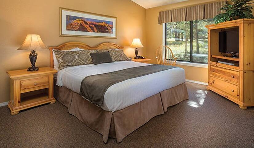 Master bedroom with a lot of space and a king size bed.