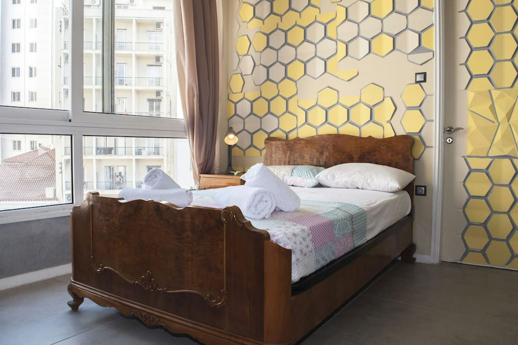 26 sq m ~Honey bedRoom with view of the Pray hands street art mural,   an indoor walk in shower with a safety double glass  &  a screen.
