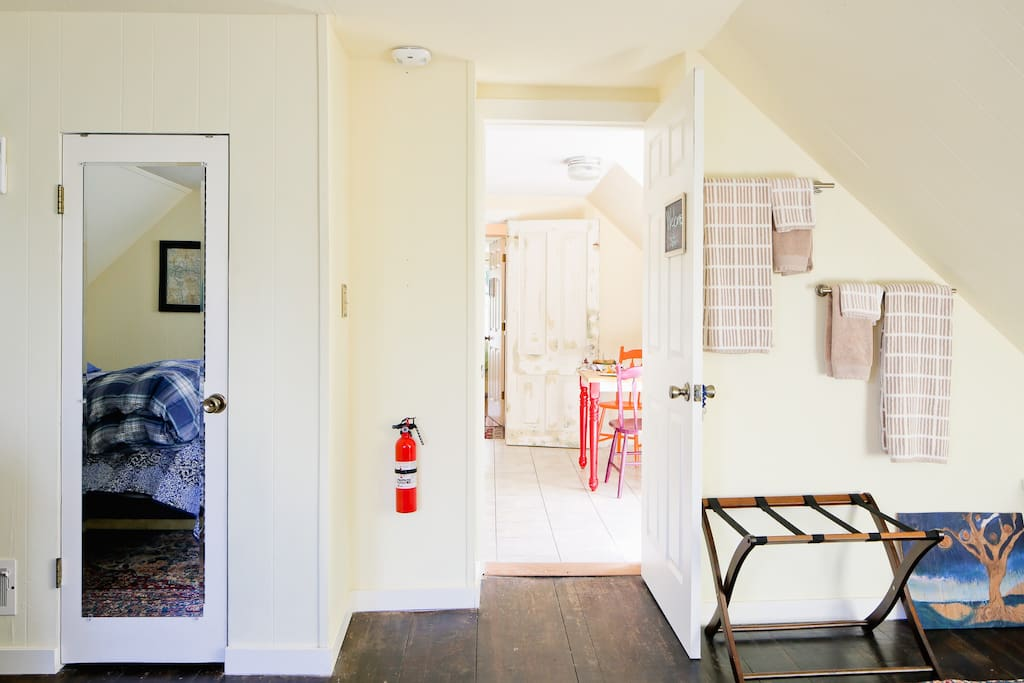 West Bedroom looking toward kitchen; towels and luggage rack behind door (w/ key).