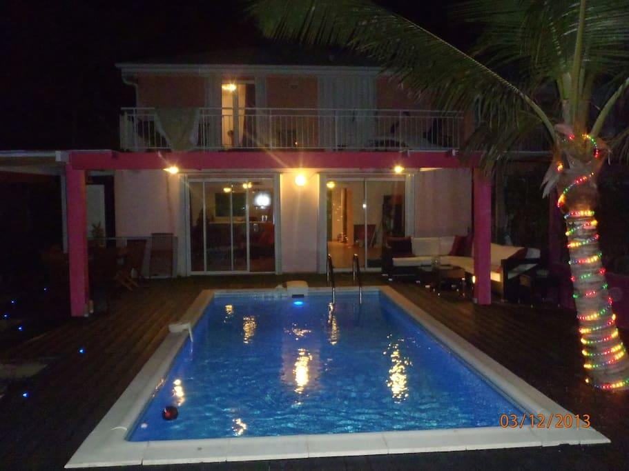 ambiance de nuit à la maison:piscine, salon à manger et salon détente.
