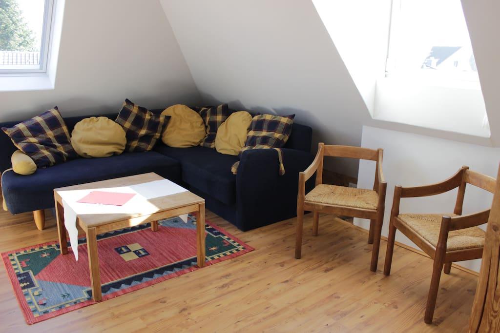 Hier das Sofa und ein ganz bisschen ist die Aussicht über Friedberg zu erahnen. Der Raum ist hell, die Fenster haben dichte Rollos für die Nacht.