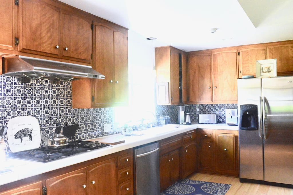 Enormous sunlit kitchen with full amenities including a coffee and cappuccino machine