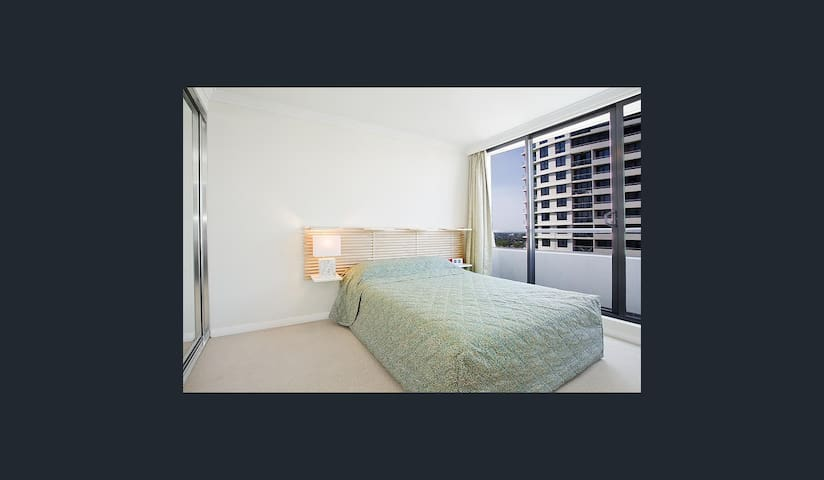 Main spacious bedroom with built-in cupboards (wall to wall) and open view to natural sunlight. Two queen pillows and a queen bed with bed lights.  Blackout curtains for privacy and to keep away sunlight are installed.