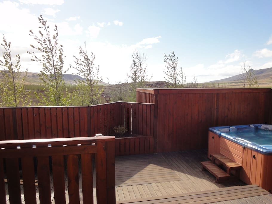 The wooden terrace with hot tub, furniture and Gas barbeque. Beautiful mountain and  forest view.