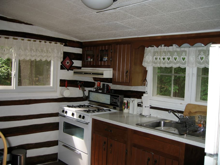 kitchen with gas cooktop and oven and new French doors (not shown in photo) windows overlook the stream.