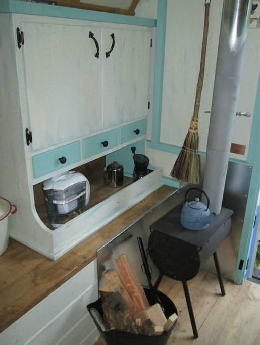 A small wood stove provide heat on cool days/night where you can also brew a pot of coffee or a cup of tea.  Dishes are provided in the cupboard.