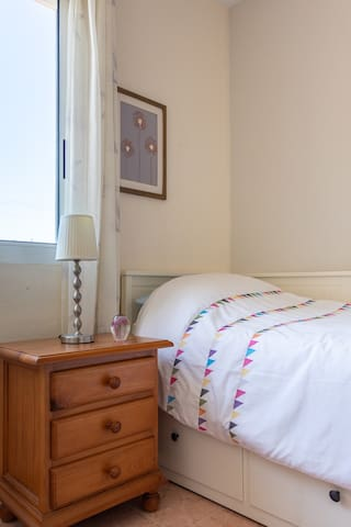 Bed can be made up as a single or comfortable double.  Large fitted wardrobe, shelving, bedside table and fan.