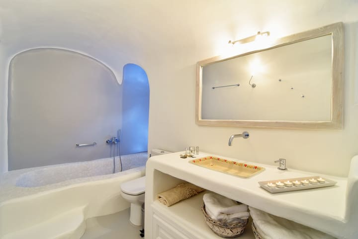 Romantic spacious bathroom with bathtub and built-in sink