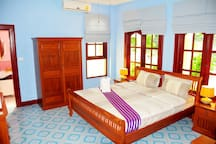Front bedroom an elegant room with impressive decor, has a king size bed, the room size is 18 square meters. Has air conditioning, ceiling fan, all teak furniture with reading lamps and ,  flat screen TV which has Rawai cable , 80 channels .