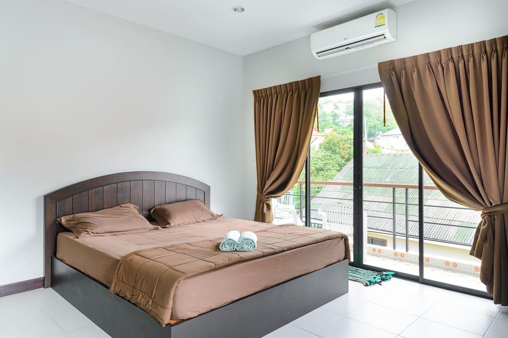 Кровать, витражное окно с выходом на балкон.