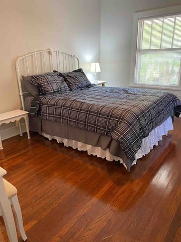 Bedroom - queen size bed, dresser, vanity with mirror and stool.