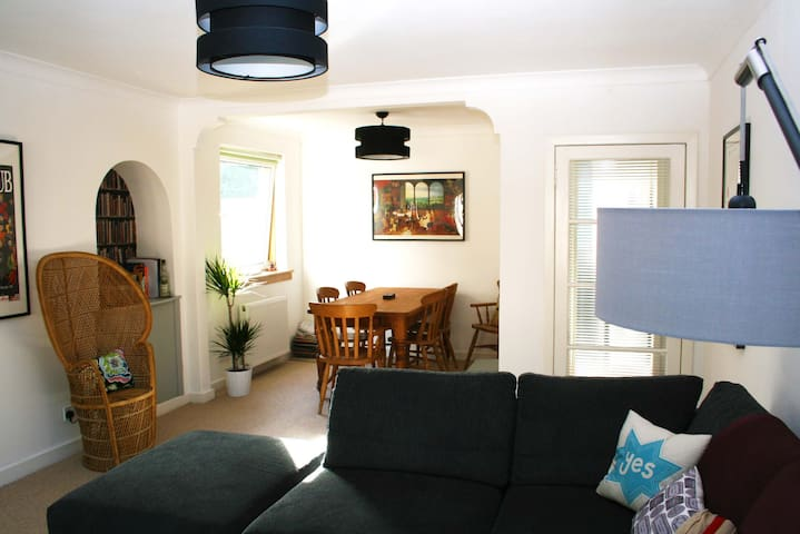 Livingroom with large corner couch, TV and dining table which seats 6.