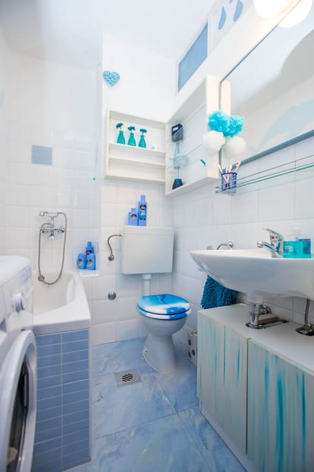 Bathroom, washing machine and bath tub with shower