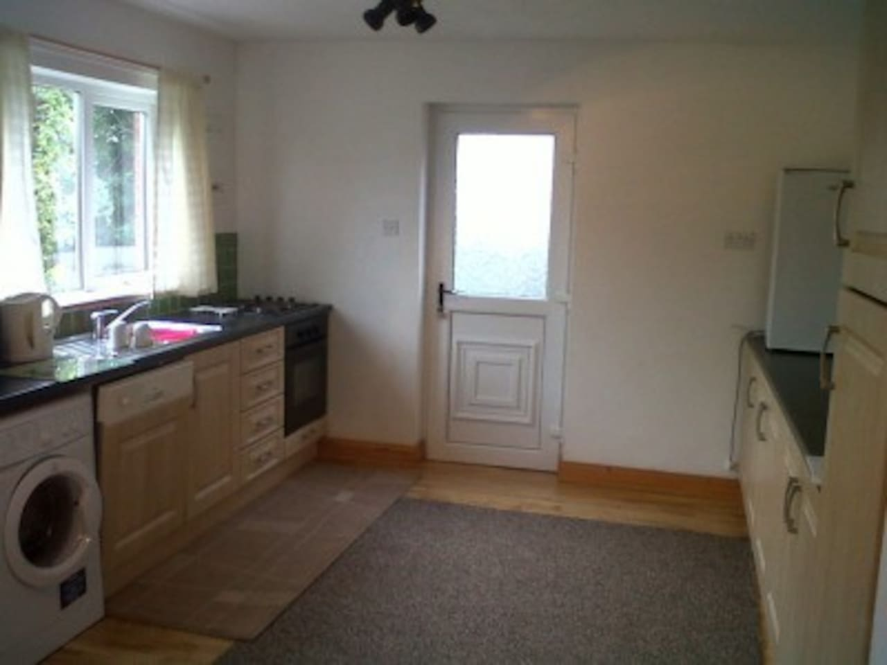 Spacious kitchen with fridge, freezer, microwave, kettle and microwave