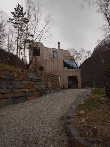 House seen from the West. Nice outdoor space in the evening. View to the fjord and the sunset.