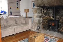 A cosy sitting room with woodburner, TV and DVD player