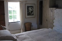 A light and airy bedroom with king size bed vies on both sides to the fields and hills