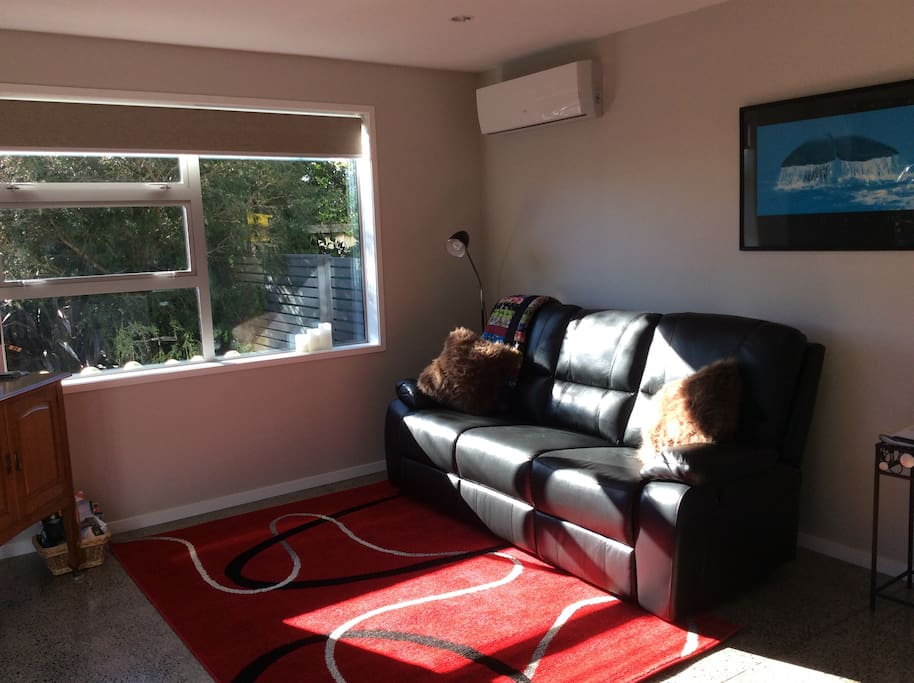 Living area-warm from sunlight and heat pump-air con available too. Luxurious new leather recliner sofa to relax on.