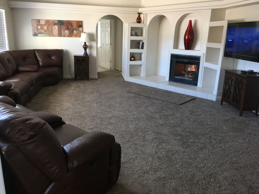 large living room with fireplace and flat screen tv.  4 reclining chairs on sectional