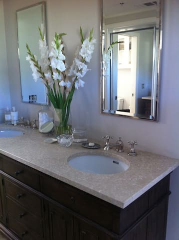 Beautiful tiled bathroom with double sink vanity.